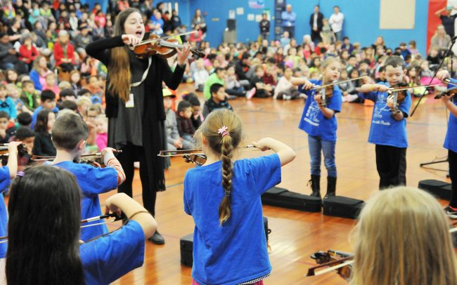 Children playing violins at a school assembly with their instructor