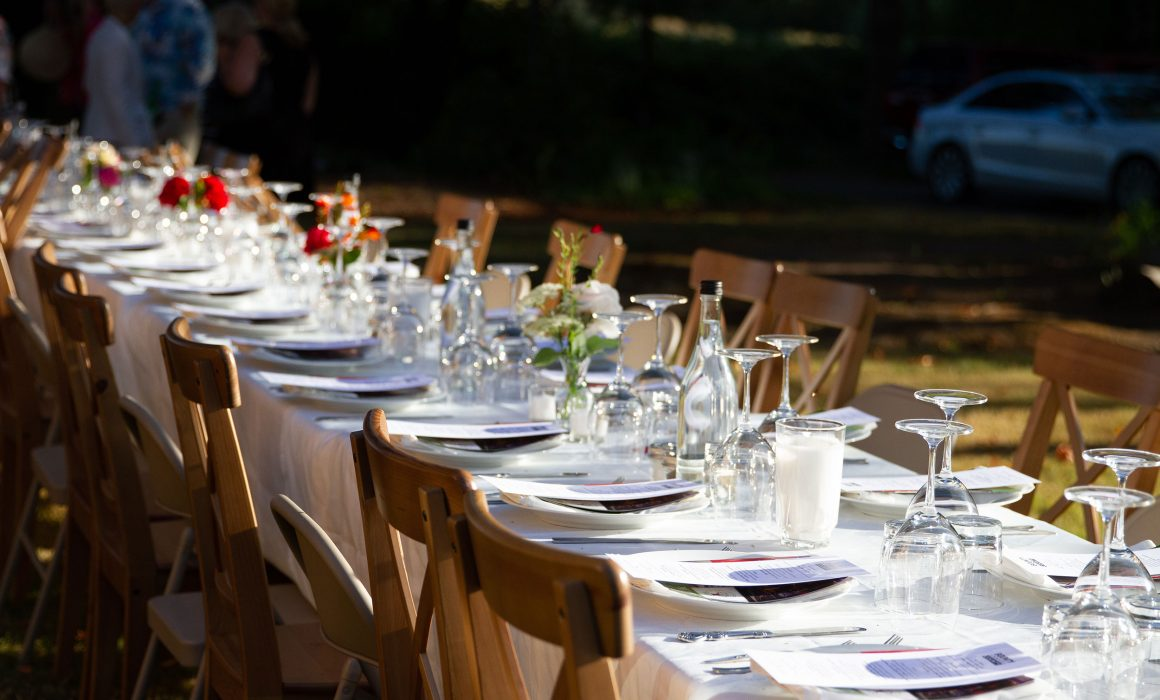 Table set outdoors farm style with glasses and wooden chairs