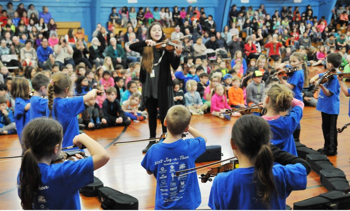 Student musicians and their instructors playing violins at assembly