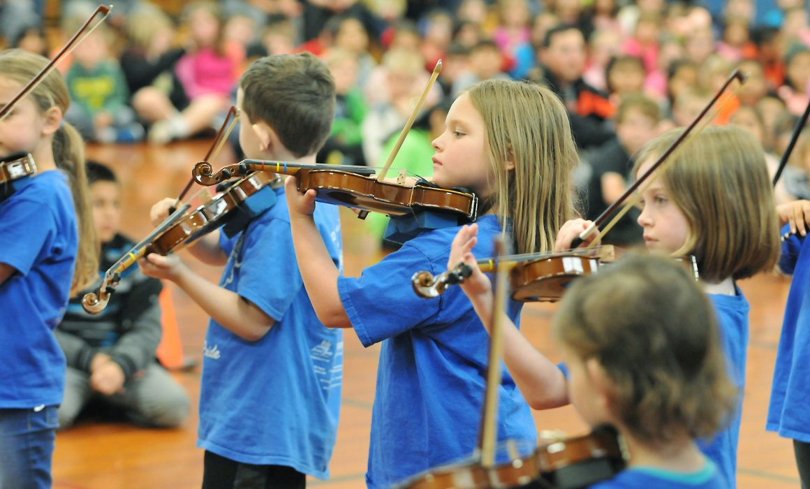 Student musicians playing violins