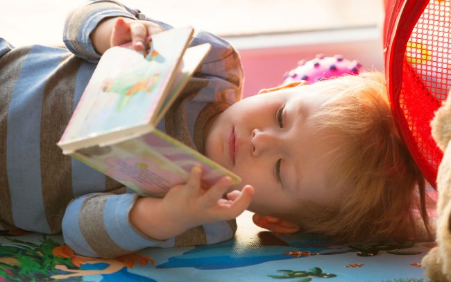 Toddler laying down reading