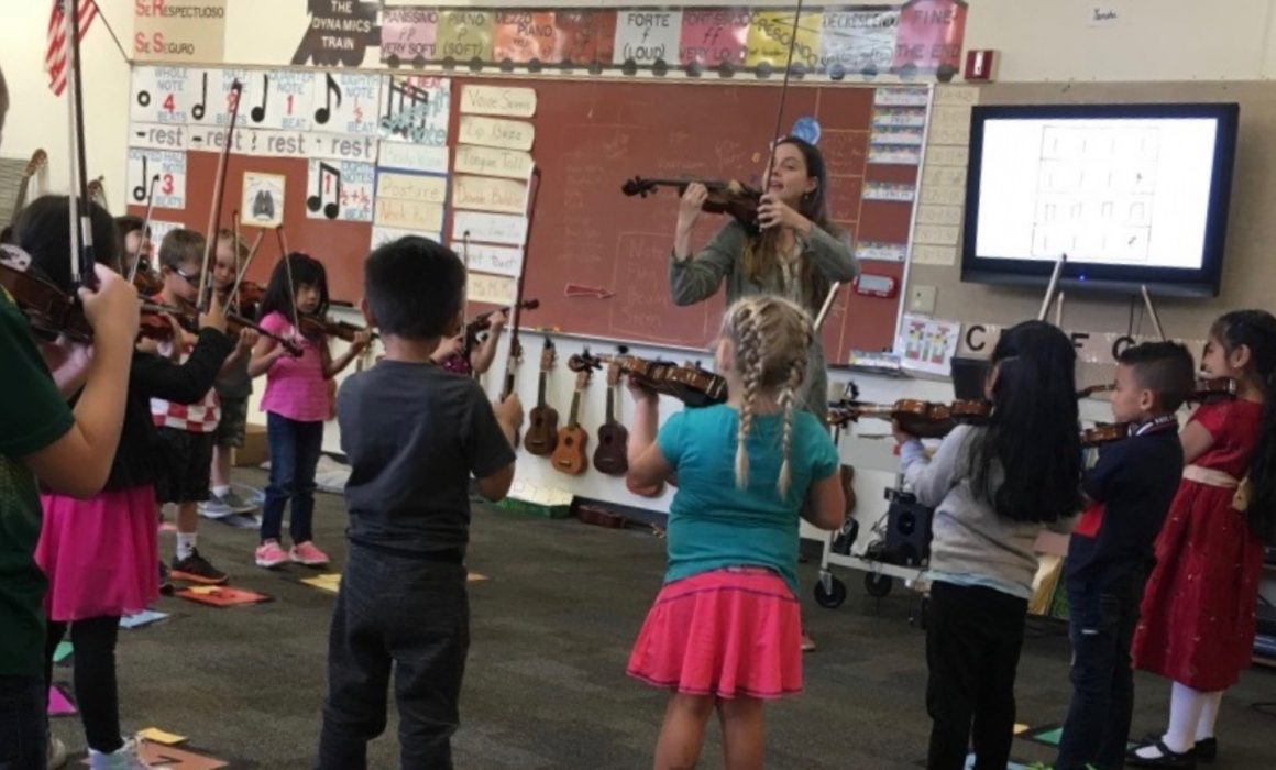 Instructor and students practicing their violins