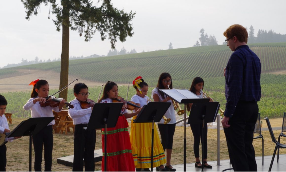 Youth Mariachi band playing at an outdoor event in a vineyard